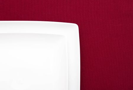 Two white plates on red cloth photo