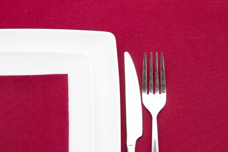 Two white square plates on red cloth with cutlery