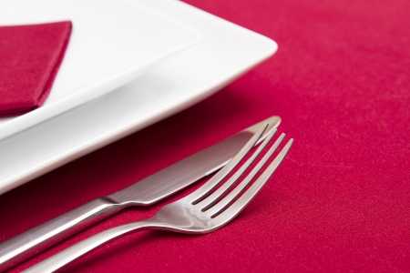 Knife and fork with white plates on red tablecloth photo