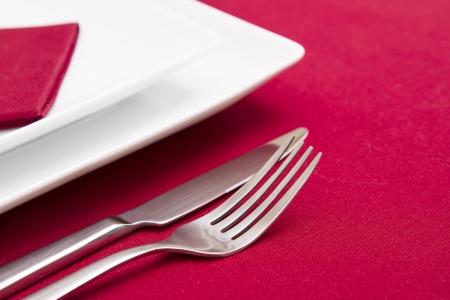 Nóż i widelec z białymi płytkami na czerwonym obrusem