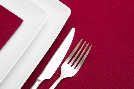 Red tablecloth with white square plates and red napkin Stock Photo