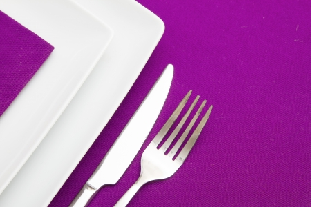 plate setting: Purple tablecloth with white square plates and mauve napkin