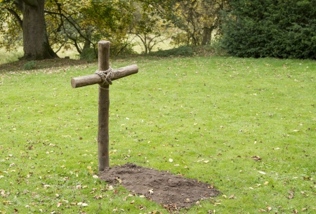 Single mock grave with wooden cross in grass field