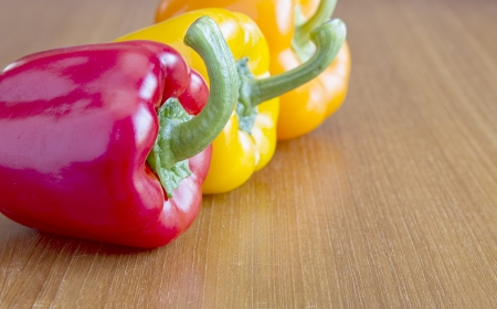 Red, yellow and orange peppers on wooden table Stock Photo - 17333560