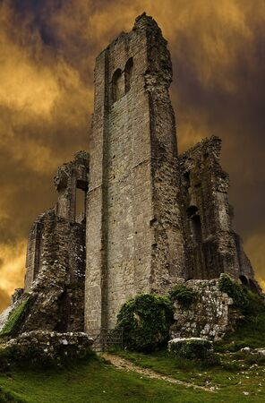 dorset: Corfe Castle ruins in evening with dark stormy sunset sky