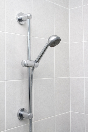 Chrome showerhead and rail on grey tiles photo