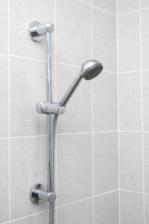 Chrome showerhead and rail on grey tiles