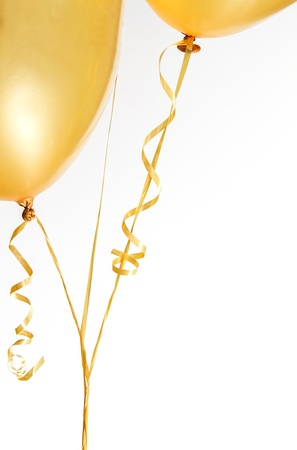 Gold balloons and ribbon on white background