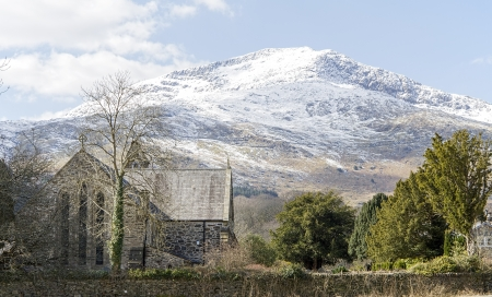 Snow covered mountain with St Marys church in Beddgelert, North Wales photo