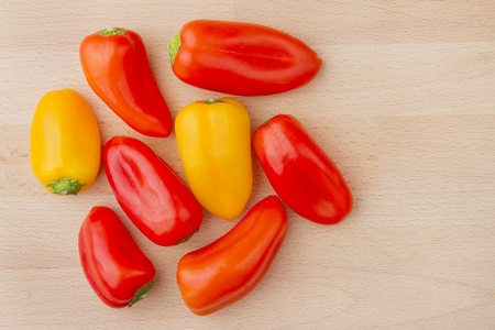 Several chiquino peppers on wooden chopping board