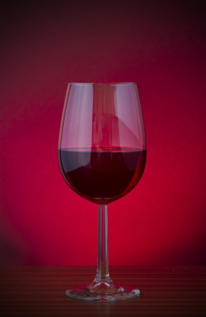 Low key vignette image of red wine in a glass photo