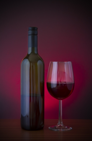 Low key vignette image of red wine in glass with bottle  photo