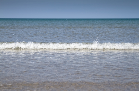 Beach with blue sky and small waves breaking at Barmouth, Wales UK photo