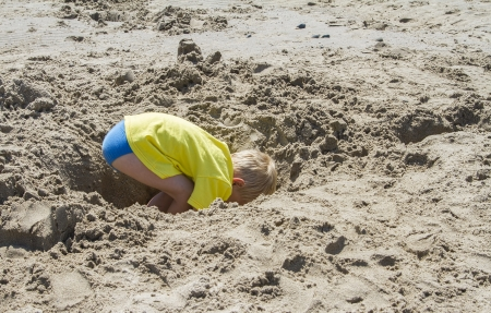 Young blond boy digging a hole in the beach photo