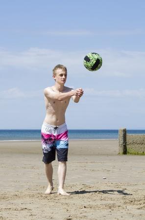 Młody mężczyzna gra w siatkówkę na piaszczystej plaży