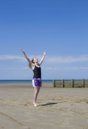 Young girl on beach raising her hands to the sky photo