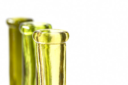 unlabelled: Three green bottles on white with shallow depth of field