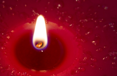 Close up glowing red candle photo