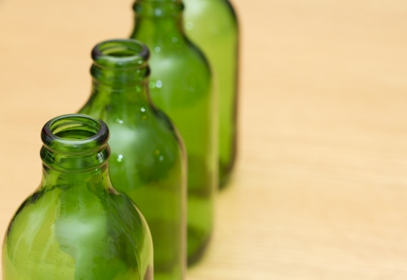 unlabelled: Top of four green bottles in a row