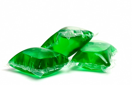 Three green laundry detergent capsules on white