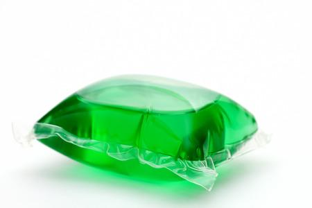 sachets: Una c�psula de detergente de lavander�a verde sobre fondo blanco Foto de archivo