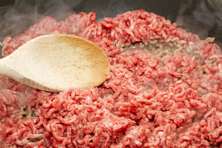 Raw mince starting to brown in pan with wooden spoon