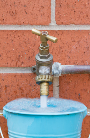 Outside tap on brick wall filling a blue bucket