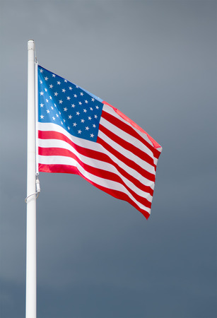 American flag on dark stormy sky photo