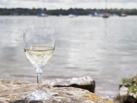 Kieliszek białego wina przez wybrzeże Zdjęcie Seryjne