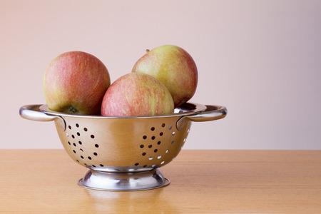 Ripe braeburn apples in a colander Stock Photo