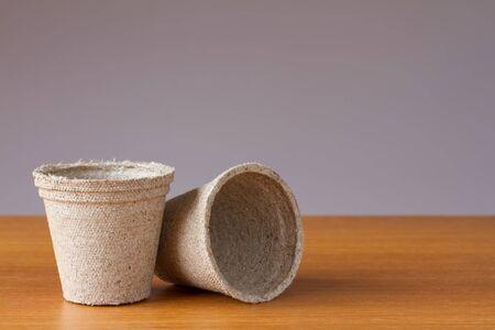 turba: Las peque�as macetas de turba en una mesa de madera Foto de archivo