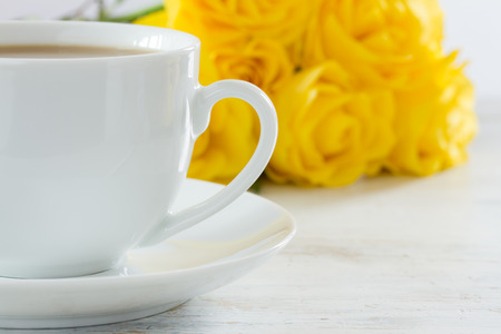 Cup of tea with a bouquet of yellow roses photo