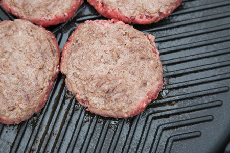 griddle: Part cooked burgers on a metal griddle Stock Photo