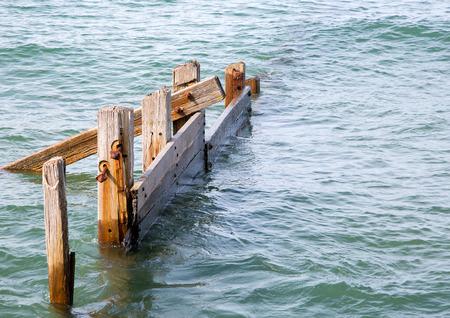 breakwaters: Old broken and weathered wooden breakwaters