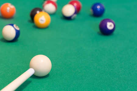 Pool balls with cue on green baize table Stock Photo