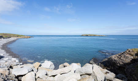 Rocky coastline at Moelfre, Anglesey in North Wales with distant view of Moelfre Island (Ynys Moelfre)