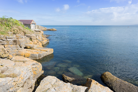 Rocky coastline at Moelfre with old lifeboat station, Anglesey North Wales