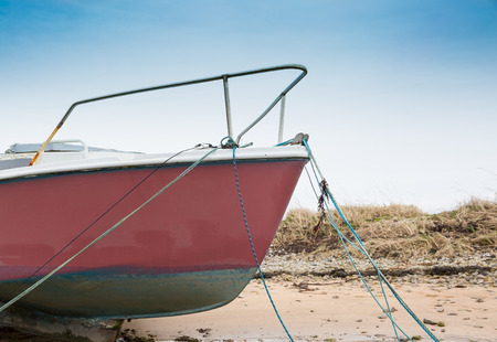 Bow of sail yaght moored at low tide Stock Photo