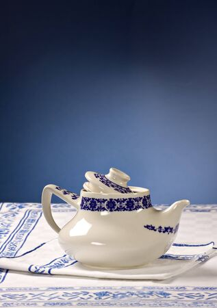 A typical retrò tea-pot on a white tablecloth and blue background.