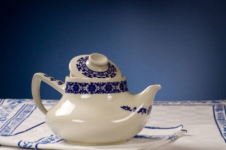 A typical retr� tea-pot on a white cloth and blue background.
