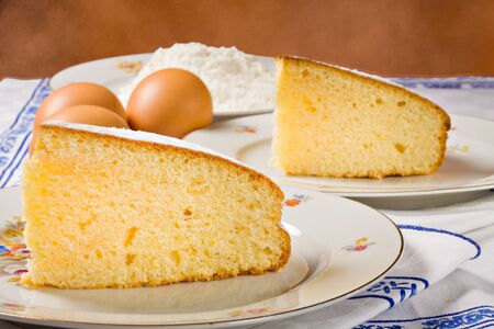 Slices of an homemade lemon cake and ingredients.