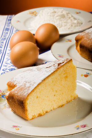 A slice of cake, homemade, and required ingredients.  photo