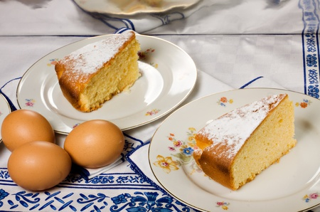 Two slices of an homemade lemon  cake and some eggs.