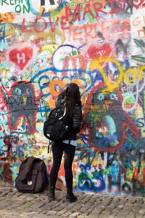 Writer at work, writing on a colorful wall in Prague (Lennons wall)