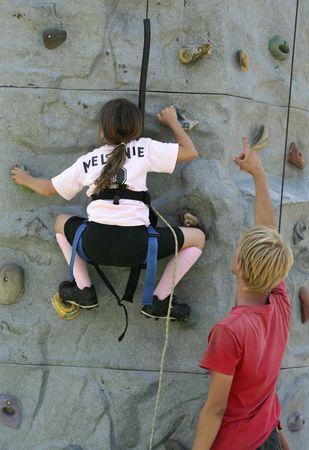 tenacity: Girl climbing up a rock wall
