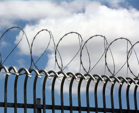 Barbed wire on top of wrought iron fencing photo