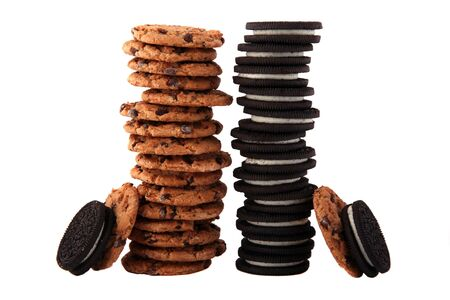Two stacks of delicious chocolate chip cookies and cream filled sandwich cookies