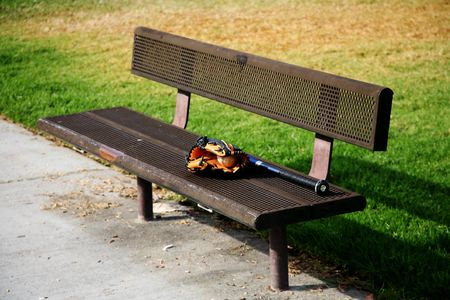 Lonely metal bench with a baseball glove and mitt on it