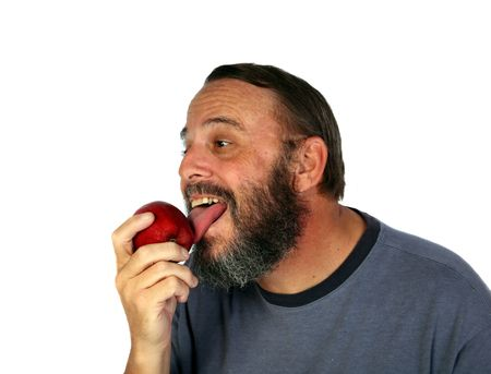 Older gentleman licking an apple prior to eating it photo