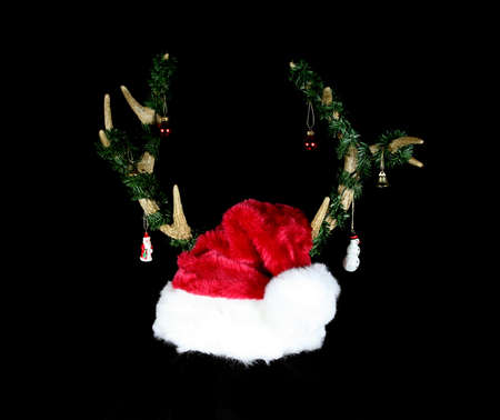 Red and white santa hat adorned with reindeer antlers isolated on black photo